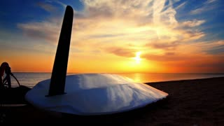 Surfboard lying on the beach at sunset. Time lapse. Sea sunset. Surf on beach at sunset. Surfboard on sand. Beach sunset. Sunset sky. Beach scene. Ocean sunset