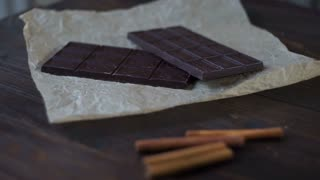 Sweet chocolate with cacao powder on wooden background. Dark chocolate bar. Black chocolate. Sweet ingredients. Sweet food. Panning on two bars of dark chocolate to cacao powder in glass