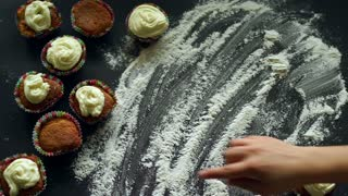 Sweet love concept. Inscription I love you on white flour. Romantic background with cupcakes cakes. Cooking dessert for valentines day. Sweet delicious. Finger writing words I love you on flour
