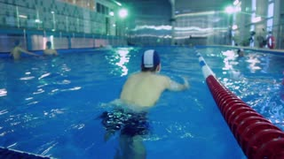 Swimming pool and swimmer during training. Training of athletes in pool. Lanes of competition swimming pool. Large indoor swimming pool for training.