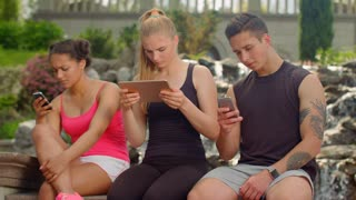 Teenage friends using digital devices outdoor. Mobile communication technology. Connection concept. Young people hanging in tablet and smartphones. Social network and mobile devices addiction