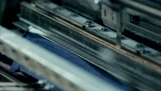 Fabric production at textile factory. Clothing production. Cotton fabric. Making clothes. Industrial equipment in textile industry. Closeup automated machine at factory. Textile industry. Fabric painting