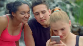 Three friends using smartphone in park. Young people talking. Cheerful friends smiling. Close up of multicultural people laughing together. Joyful people having fun in park. Friends surfing internet