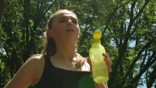 Tired woman holding sport bottle with cold water in hand. Fatigue woman in park. Close up of fitness woman resting after running outdoor at summer. Thirsty woman hold plastic bottle with liquid