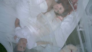 Top view of love couple relaxing on white fabric behind transparent veil in park. Romantic holiday. Closeup of two people lying in romantic decoration. Romantic couple resting outdoor