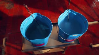 Two buckets with disinfectant. Worker takes cleaning brush from water in buckets. Cleaning equipment. Dairy food processing plant