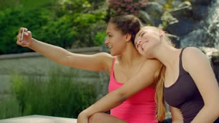 Two girlfriends taking photos in park. Girls selfie outdoor. Happy girlfriends smiling. Lesbians taking selfie at nature. Multicultural people taking picture. Young women posing on phone camera