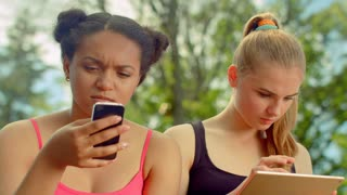 Two young women using digital devices. Digital lifestyle. Women mobile technology. Internet addiction. Multiracial friends hanging in social networks. Students using wireless internet in park