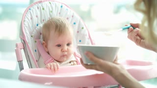 Absently baby not eating puree. Woman feeding kid. Pretty baby girl in chair. Mother feeding daughter. Mom try to feed tired toddler. Infant eating dinner. Family care