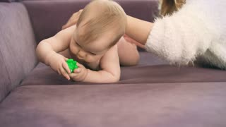 Adorable baby crawl on violet bed. Cute child with toy trying crawling. Happy mom looking on baby. Naked child in diapers gnawing toy. Funny kid with mom at home. Beautiful mother and daughter play