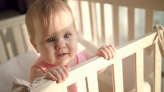 Adorable baby reach out hand in cot. Beautiful toddler standing in crib and reaching out to mother. Portrait of cute baby in bed at sunny room. Little child with interesting face