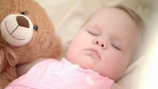 Adorable baby sleeping in bed. Close up of infant girl sleeping with toy. Sweet child face in crib. Dream time for toddler. Kids lullabies. Bedtime concept. Portrait of sleeping baby