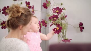 Adorable baby touching flowers at home. Infant child on mother hands touch violet chamomile flower. Little kid eating beautiful flowers in vase. Child exploring world. Stylish mother holding baby