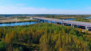 Aerial bridge landscape. Aerial view highway bridge over river. Cars driving along highway bridge. Aerial highway road over river. Sky view highway on river landscape. Aerial road bridge