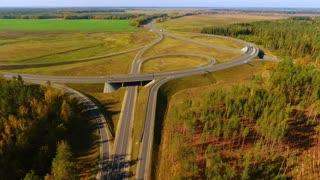 Aerial highway. Highway junction. Winding road. Top view cars driving on road junction. Cars traffic at highway junction aerial. Aerial view road intersection in field. Highway road