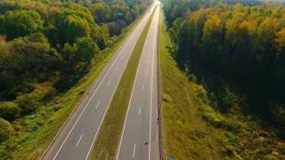 Aerial landscape of highway road at forest. Drone landscape of road in autumn forest. Cars driving on highway road between trees. Aerial view of asphalt road in forest landscape. Highway traffic