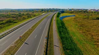 Aerial motorway. Cars moving on highway road. Cars and trucks driving on country road. Highway road aerial landscape. Aerial view of cars traffic on highway road. Drone view highway landscape