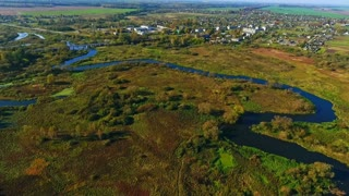 Aerial river landscape. River in forest. View from above. Sky view of meandering river in forest near city. Aerial landscape river forest. Drone view of city near autumn forest