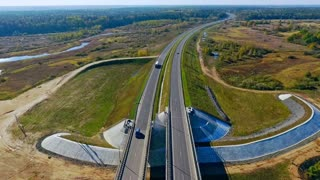 Aerial road bridge above river. Top view cars and truck moving on highway bridge. Aerial view of straight highway road above river. Drone view of automobile traffic on bridge above river