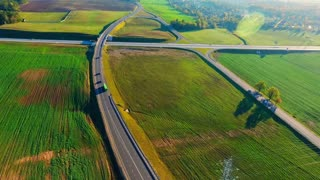 Aerial view cars moving on highway intersection in green fields. Aerial landscape road junction. Aerial highway road top view. Aerial highway crossing in nature landscape. Crossing road sky view