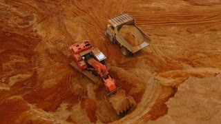 Aerial view mining excavator loading dumper truck. Heavy machinery working at sand mine. Crawler excavator pouring sand at mining truck. Mining industry. Mining machinery working in sand pit