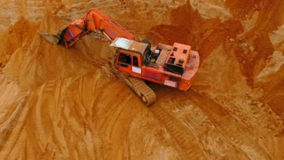 Aerial view of crawler excavator standing on sand mine. Sky view of mining equipment on background sand mountain. Top view of mining machinery standing on territory industrial sand mine. Sand mining