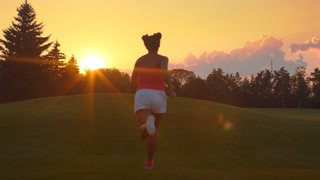 African woman jogging in park. Mulatto girl running sunset. Young woman running back. Back view of mulatto woman running hill at sunrise. Running woman at sunset sky background