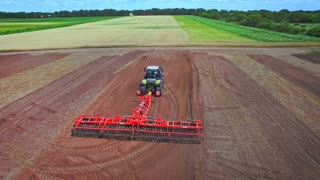 Agricultural machinery working on agricultural field. Agricultural vehicle plowing farming field. Aerial view process cultivation ploughing field. Farming industry. Soil preparation. Tractor in field