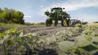 Agricultural sprayer and farming equipment standing on field. Agricultural equipment on farming field. Agricultural industry. Farming agriculture. Farming machinery. Agricultural machinery
