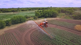 Agricultural sprayer irrigating plant on farming field. Aerial view process watering field. Spraying machine agriculture irrigation. Farming industry. Agriculture watering
