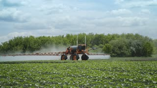 Agricultural sprayer watering farming field. Agriculture spraying machine working on agricultural field. Farmer care plants. Pesticides spraying
