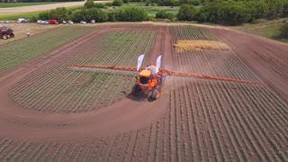 Agricultural sprayer watering plant on farming field. Drone view agriculture irrigation on cultivated field. Spraying machine watering field. Agricultural irrigation equipment. Agriculture watering