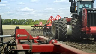 Agricultural tractor driving on arable field for plowing land. Farming tractor working on farming field. Agricultural machinery on plowing field