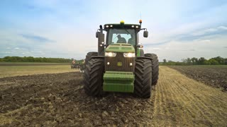 Agricultural tractor moving on field. Agricultural equipment working on field. Cultivation agricultural field with harvester machine. Agricultural industry. Agriculture machinery