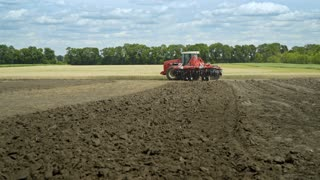 Agricultural tractor plowing farming field. Farming tractor on agricultural field. Farming machinery on plowing field