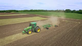 Agricultural tractor plowing farming field. Farming tractor working on cultivated field. Aerial view agricultural vehicle plowing farming field. Agricultural machinery. Farming aerial