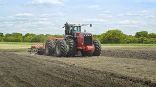 Agricultural tractor with plowing trailer working on farming field. Farming tractor plowing agricultural field. Agricultural machinery for plowing land