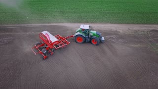 Agricultural tractor with seeder moving on plowed land. Sowing machine working on agricultural field. Drone view sowing process on farming field. Farming industry. Agriculture machine