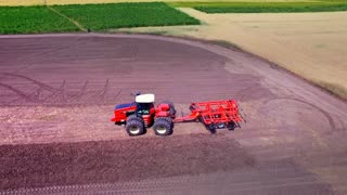 Agricultural tractor with trailer for ploughing working on cultivated field. Drone view agricultural vehicle on farming field. Farming tractor plowing agricultural field. Rural farming. Farming aerial