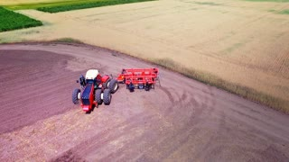 Agricultural tractor with trailer for ploughing working on cultivated field. Process plowing agricultural field. Aerial view farming tractor plowing agricultural field. Agricultural technology