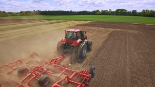 Agricultural tractor with trailer plowing on farming field. Sky view farming tractor driving on plowing field. Agricultural industry. Farming machinery. Agricultural sector. Tractor ploughing