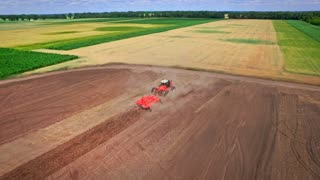 Agricultural tractor with trailer plowing ploughing field. Drone view farming tractor plowing field. Agricultural machinery working on rural field. Agricultural industry. Aerial agriculture field plow