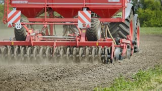 Agricultural tractor with trailer seeder working on plowed field. Sowing machine driving on plowed field. Sowing process on agricultural field. Agricultural industry. Rural farming. Sowing seeds