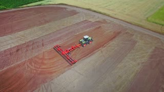 Agriculture industry. Farming tractor with trailer plowing agricultural field. Agricultural vehicle plowing farming field. Aerial view process cultivation ploughing field. Aerial agricultural field