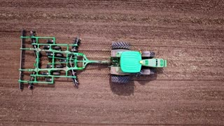 Agriculture machinery. Agricultural tractor plowing arable field. Farming tractor working on cultivated field. Sky view agricultural vehicle plowing farming field. Agricultural ploughed field
