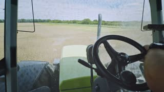 Agriculture tractor driver point of view. Driving tractor on agriculture field. Tractor steering wheel hand