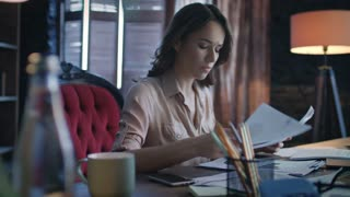Annoyed businesswoman answering on mobile phone call while working with paper documents. Business woman in bad mood talking on smartphone in office at evening