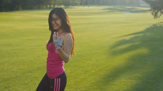 Asian woman having fun on green meadow. Happy woman dancing in slow motion at summer park. Cheerful woman turning around. Joy and happiness concept. Sexy girl flirting with camera