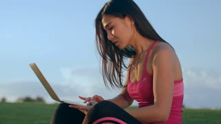 Asian woman working with laptop computer in park. Young woman using notebook outdoors. Female student working with laptop at sky background. Real woman laptop outdoors. Mobile working
