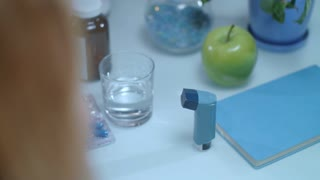 Asthma inhaler on table. Medical equipment on treatment of asthma attack. Close up of woman breathing asthma inhaler. Health care of asthmatic patient